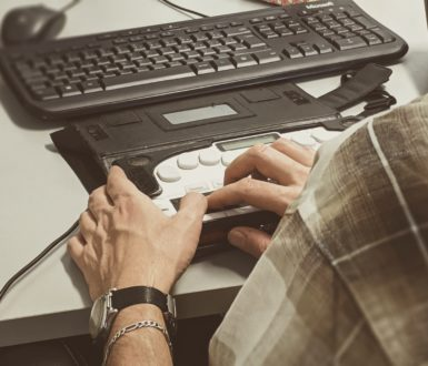 Man's hands shown typing on braille keyboard alongside standard keyboard